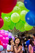25 JULY 2014 - BANGKOK, THAILAND:  A Thai woman with balloons at the party restore happiness to the people at Ratchaprasong Intersection. The party was organized and sponsored by the Tourism Authority of Thailand and was promoted as an effort to restart Thailand's tourism industry, which has seen a significant drop in foreign arrivals since political violence started in 2013. There has been no violence since the coup on May 22, 2014, but tourism has not completely rebounded.    PHOTO BY JACK KURTZ