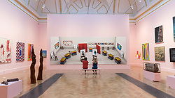 """© Licensed to London News Pictures. 05/06/2018. LONDON, UK. Staff members view """"Seven Trollies, Six and a Half Stools, Six Portraits, Eleven Paintings and Two Curtains"""" by David Hockney RA at a preview of the 250th Summer Exhibition at the Royal Academy of Arts in Piccadilly, which has been co-ordinated by Grayson Perry RA this year.  Running concurrently, is The Great Spectacle, featuring highlights from the past 250 years.  Both shows run 12 June to 19 August 2018.  Photo credit: Stephen Chung/LNP"""
