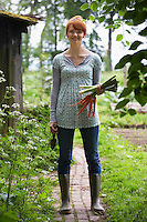 Woman holding carrots and leeks in garden portrait