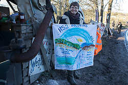 Harefield, UK. 19 January, 2020. Sarah Green of Save The Colne Valley holds a handpainted banner at the Colne Valley wildlife protection camp. Activists from Extinction Rebellion, Stop HS2 and Save the Colne Valley attending a 'Stand for the Trees' event timed to coincide with tree felling work for HS2 have retaken the camp from which a small group of Save the Colne Valley activists had been evicted by bailiffs acting on behalf of HS2 over the previous week and a half. 108 ancient woodlands are set to be destroyed by the high-speed rail link.