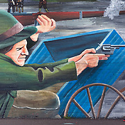 A pedestrian seemingly walks into aim walking by a mural in Northern, Ireland.  - Leica 240 MP / 135 mm