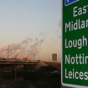 UK direction sign showing towns in the midlands main routes with power station in the foreground