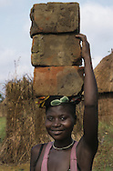 Ugandan woman carries home made bricks