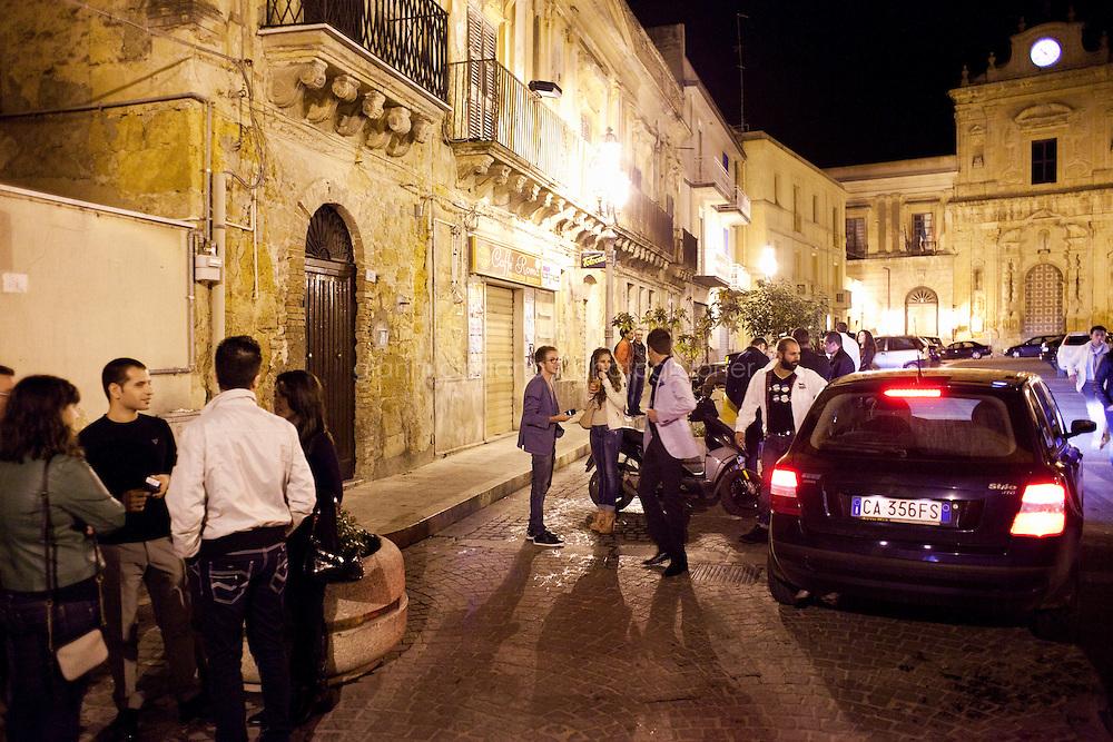 Naro, Italia - il 15 September 2012: dei ragazzi frequentano l'Happy Hour Café in piazza Garibaldi, di fronte alla chiesa di San Francesco a Naro, Italia, il 15 September 2012.