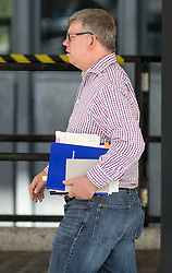 """© Licensed to London News Pictures. 06/07/2016. London, UK. A man leaves QEII Cente on the day Sir John Chilcot's The Report of the Iraq Inquiry is published, with a note in the volume he is carrying reading """"did Hitler"""". The Inquiry was predicated to take approximately one year, but has taken seven. Photo credit : Tom Nicholson/LNP"""