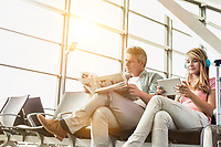 Young beautiful teenage girl watching movie on digital tablet with headphones on while her father is reading newspaper in airport