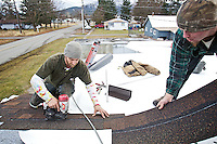 """Zeke Smith, left, and Britton Profant, with Precision Roofing, secure shingles to Larene """"Billie"""" Stone's roof Tuesday. Precision Roofing donated the labor to repair the leaky roof."""