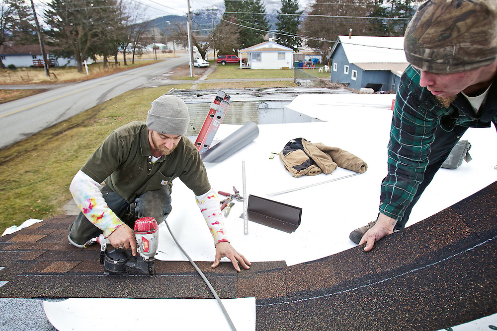 "Zeke Smith, left, and Britton Profant, with Precision Roofing, secure shingles to Larene ""Billie"" Stone's roof Tuesday. Precision Roofing donated the labor to repair the leaky roof."