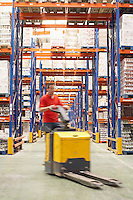 Mid-adult Man Driving Pallet Jack Through Warehouse