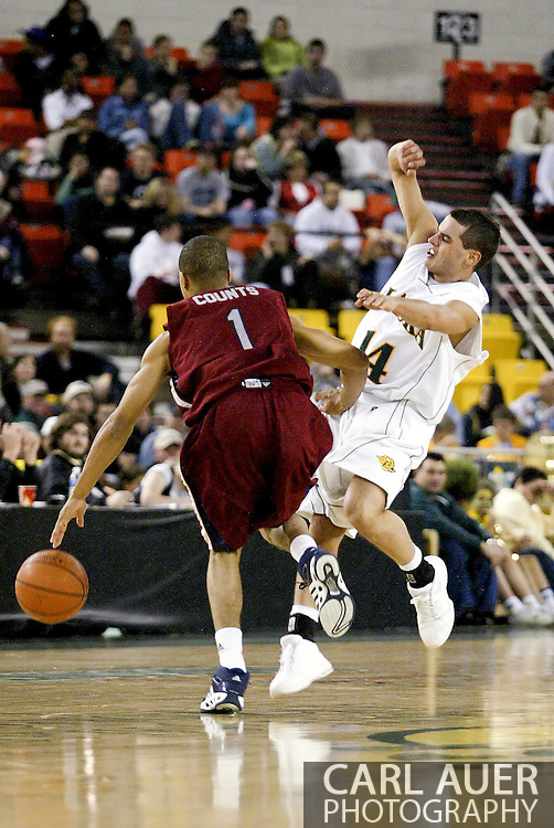 11/22/2006 - Anchorage, Alaska: Junior guard Luke Cooper (14) of the UAA Seawolves tries to draw a charge from Corey Counts (1) as Loyola Marymount defeats the University of Alaska-Anchorage 69-58 in the first game of the 2006 Great Alaska Shootout<br />