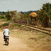 A man rides a bicycle along a set of railway tracks in rural Cuba.