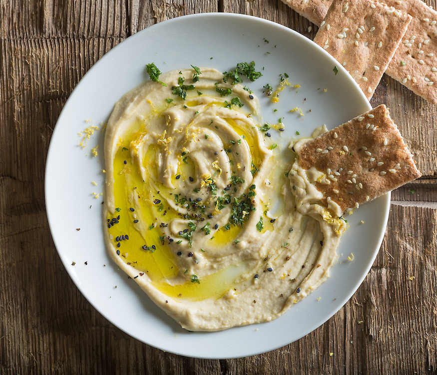 Plate of hummus with olive oil, spices and crackers.