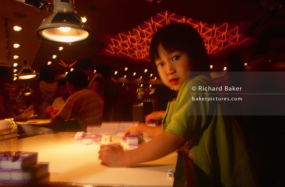 A young girl plays with Mahjong tiles at a night-club, on 10th August 1994, in Macau, China. The Macau Special Administrative Region is one of the two special administrative regions of the People's Republic of China (PRC), along with Hong Kong. Administered by Portugal until 1999, it was the oldest European colony in China, dating back to the 16th century. The administrative power over Macau was transferred to the People's Republic of China (PRC) in 1999, 2 years after Hong Kong's own handover.