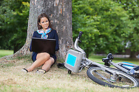 Portrait of young businesswoman with laptop and bicycle sitting at park