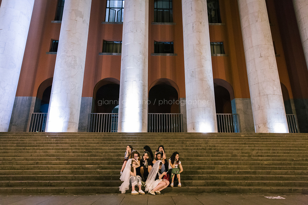 PALERMO, ITALY - 15 JUNE 2018: A group of young women is seen here by the central Post Office of Palermo at late night during Manifesta 12, the European nomadic art biennal, in Palermo, Italy, on June 15th 2018.<br /> <br /> Manifesta is the European Nomadic Biennial, held in a different host city every two years. It is a major international art event, attracting visitors from all over the world. Manifesta was founded in Amsterdam in the early 1990s as a European biennial of contemporary art striving to enhance artistic and cultural exchanges after the end of Cold War. In the next decade, Manifesta will focus on evolving from an art exhibition into an interdisciplinary platform for social change, introducing holistic urban research and legacy-oriented programming as the core of its model.<br /> Manifesta is still run by its original founder, Dutch historian Hedwig Fijen, and managed by a permanent team of international specialists.<br /> <br /> The City of Palermo was important for Manifesta&rsquo;s selection board for its representation of two important themes that identify contemporary Europe: migration and climate change and how these issues impact our cities.