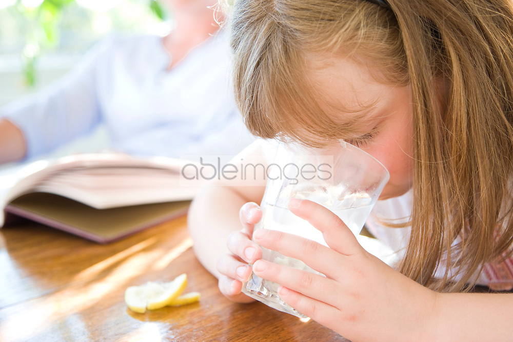 Girl Drinking Water with Ice and Lemon