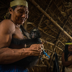 A man from the Huaorani tribe is playing with his pet monkey, Yasuni Reserve, Ecuador.