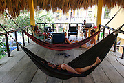 Group of European tourists resting on hammocks. Photographed at El Tunco beach, El Salvador,