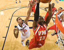Virginia Military guard Travis Holmes (23) dunks past Virginia guard Sylven Landesberg (15).  The Virginia Cavaliers defeated the Virginia Military Institute Keydets 107-97 in NCAA Basketball at the John Paul Jones Arena on the Grounds of the University of Virginia in Charlottesville, VA on November 16, 2008.