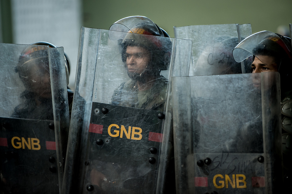 CARACAS, VENEZUELA - JULY 26, 2017: Soldiers take cover behind shields, as protesters throw rocks and Molotov cocktails at them, during an anti-government protest to demand that the National Constituent Assembly election scheduled for Sunday, July 30th be cancelled. The political opposition called for a 48 hour national strike on July 26th and 27th, and for their supporters to close businesses, not go to work, and instead create barricades to block off their streets.  Opposition controlled areas of the country were completely shut down.  The strike was called as part of the opposition's civil resistance movement - that began on April 1st, to protest against the Socialist government's attempt to elect a new assembly that will have the power to re-write the constitution, and their opposition to the Socialist's continued threats to Venezuelan Democracy.  PHOTO: Meridith Kohut for The New York Times