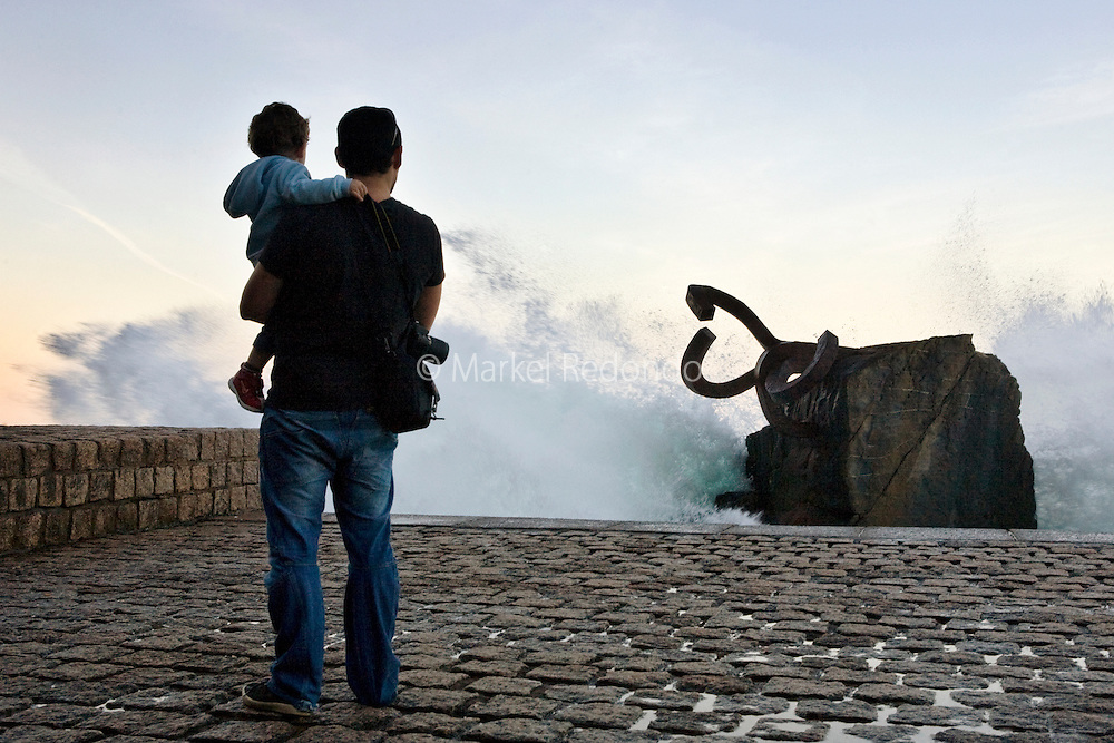 A man with his son at Comb of Wind, in San Sebastian, Spain.
