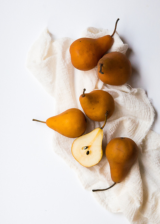 Fresh Bosc pears laying on cheese clothe stilllife