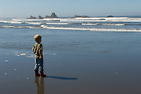 5 year old boy looks out on the ocean from a beach on the Olympic Peninsula.