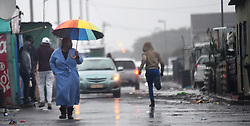 SOUTH AFRICA  - Cape Town - 26 May 2020 - A man runs past a woman with an ambrella as he looks for cover on the streets of Joe Slovo in Langa t,for the past 3 days the Western Cape has been having a bad weather .photograph;Phando Jikelo/African News Agency(ANA)