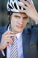 Portrait of young businessman adjusting helmet