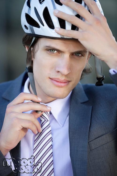 Portrait of young businessman adjusting helmet
