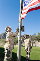 Soldiers raising United States flag outdoors