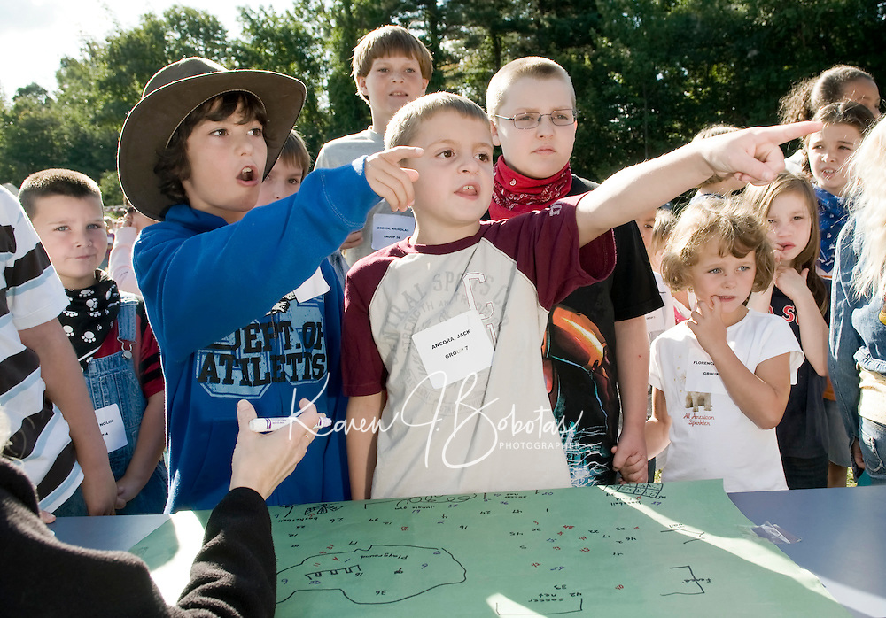 """Gold Diggers Troy Minor and Jack Ancora show Special Education teacher and """"map documenter"""" Debbie Brooks exactly where they found their gold during Elm Street School's Community Day Gold Rush on Tuesday morning.  (Karen Bobotas/for the Laconia Daily Sun)"""