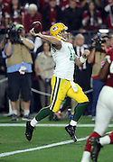 Green Bay Packers quarterback Aaron Rodgers (12) throws a 60 yard pass for a first down at the Arizona Cardinals 36 yard line on a fourth down play with 20 yards to go for a first down and under one minute left in the fourth quarter during the NFL NFC Divisional round playoff football game against the Arizona Cardinals on Saturday, Jan. 16, 2016 in Glendale, Ariz. The Cardinals won the game in overtime 26-20. (©Paul Anthony Spinelli)