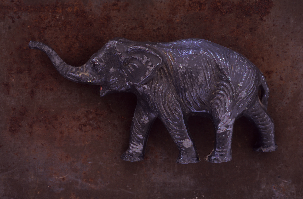 Close up of battered and scratched lead model of grey elephant walking with its trunk raised lying on rusty metal sheet