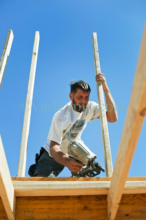 26 August 2015. New Orleans, Louisiana. <br /> Hurricane Katrina revisited. <br /> Rebuilding the Lower 9th Ward. <br /> Terry Gauxtreaux, a contractor with Welbilt homes works on a new 'Make it Right' house on Tennessee Street. Eco friendly 'Make it Right' houses inspired by actor Brad Pitt continue to provide hope for the rebirth of the community following the devastation of hurricane Katrina a decade earlier.<br /> Photo credit©; Charlie Varley/varleypix.com.