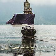 INDONESIA. Bedugul, Bali. June 4th, 2013. Inside the Pura Ulun Danu Bratan complex, this stone alter provides an offering on Lake Bratan.