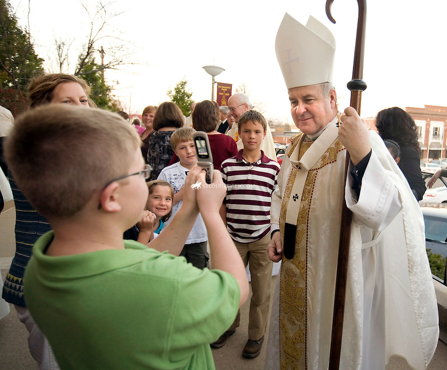 "SUNDAY, NOV. 22, 2009 - Seth Martin, 10, takes a photograph of Archbishop Robert Carlson after Mass Sunday outside Ste. Genevieve which was celebrating its 250th anniversary as a parish..""I never saw a real bishop before,"" said Seth. ""I only saw one on TV..""Well, I'm a real bishop,"" Carlson said with a smile...©Photo by Jerry Naunheim Jr.... .."