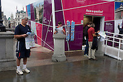 Tourists inspect city maps provided free by volunteers at a London 2012 Olympic information kiosk in the capital's Trafalgar Square.