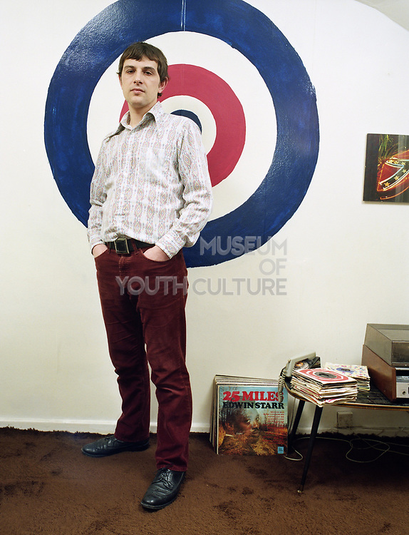 Young man dressed in Mod clothing standing in front of a Royal Air Force roundel,  symbol of Mod culture.