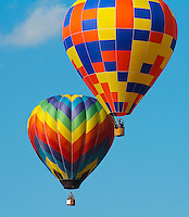 """Two Hot Air Balloons image for sale, A hot air balloon for manned flight uses a single-layered, fabric gas bag (lifting """"envelope""""), with an opening at the bottom called the mouth or throat. Attached to the envelope is a basket, or gondola, for carrying the passengers. Mounted above the basket and centered in the mouth is the """"burner"""", which injects a flame into the envelope, heating the air within. The heater or burner is fueled by propane, a liquefied gas stored in pressure vessels, similar to high pressure forklift cylinders."""