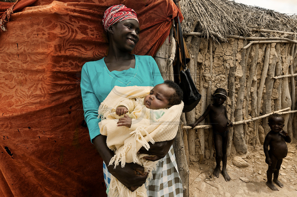 Tchikuteny?s wife and baby at the village. In Angola?s Namibe desert, at Giraul, in the Namibe province, Tchikuteny, from the Mucubal tribe, is the leader of a big family, maybe the biggest family in the world.<br /> He is the chief leader, the manager and responsible for the entire village. <br /> In his village, Tchikuteny lives nowadays with most of his big family, his 33 wives, that were once 43, but 10 left the village, and most of their descendants.<br /> Tchikuteny maintains the registry of all the new-borns, totalizing 154 sons, and his grandsons, that are around 60. Nowadays, 4 new babies are on the way, and 3 great grand children were born recently.<br /> Huge harmony, love and respect transpire in the village atmosphere. The sense of a community is the pillar of their sustainability and sustenance and their autonomy depends prominently on cattle and agriculture that is made by the villagers. Nevertheless, Tchikuteny village is in close connection with their surrounding communities. Children attend Giraul School and there is proximity and relations with the extended family that lives in the surroundings.<br /> Being the spiritual leader of the community, Tchikuteny is also responsible for the weekly religious works that happens in the village church. <br /> This big family opened his doors to share with us their daily lives.