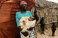 Tchikuteny?s wife and baby at the village. In Angola?s Namibe desert, at Giraul, in the Namibe province, Tchikuteny, from the Mucubal tribe, is the leader of a big family, maybe the biggest family in the world.<br />