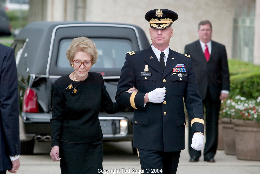 Nancy Reagan leaving the Reagan Library to follow her husbands remains for transport to Pt. Magu for a flight to Wash. DC..Former first lady Nancy Reagan (L) is escorted by Maj. Gen Galen B. Jackman while the casket of former President Ronald Reagan is placed into the hearse for transport to the Pt. Mugu Naval Air Station at the Ronald Reagan Presidential Library June 9, 2004 in Simi Valley, California. ..Ronald Reagan Library, Simi Valley, CA USA 6/9/04.