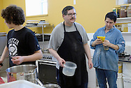 Canada, Ontario, Kitchener. February 21, 2008. Clean-up and food preparation at the Working Centre's Maurita's Kitchen. The Working Centre is a volunteer inspired organisation that provides individuals and groups certain tools for community  building.