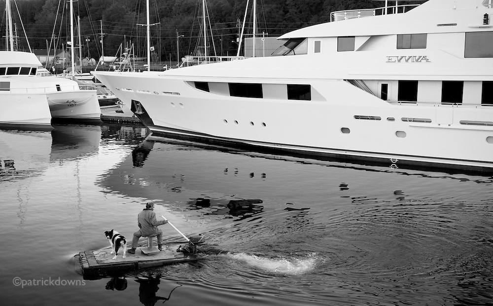 """Rich boat, poor boat: A harbor worker and his dog, on a workboat that is little more than a plank with a motor, cruises past the $40 million dollar yacht """"Evviva."""" Port Angeles WA"""