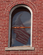 An American flag is reflected in one of the third floor windows of the Holy Childhood Building in Harbor Springs.