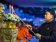20 JANUARY 2017 - BANGKOK, THAILAND: Pol Gen ASWIN KWANMUANG, the Governor of Bangkok, lights candles to honor Bhumibol Adulyadej, the King of Thailand, on the plaza in front of Bangkok's City Hall. Hundreds of municipal workers and civil servants made merit by praying and presenting alms to 89 Buddhist monks Friday to mark 100 days of mourning since the death of revered King. The significance of 89 monks is that the King, who died on October 13, 2016, was a few weeks short of his 89th birthday.        PHOTO BY JACK KURTZ