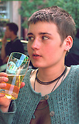 Girl age 19 drinking a beer at outside sidewalk cafe.  Warsaw Poland