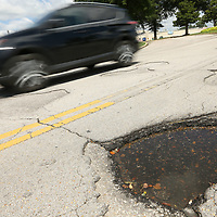 A car drives over the potholes on Mall Drive on Monday at The Mall at Barnes Crossing in Tupelo.