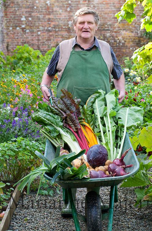 John Harris with a wheelbarrow full of colourful harvested vegetables